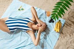 Mujer joven bronceada que toma el sunbath malsano en un día de verano en una playa que oculta del sol con el sombrero y los vidri Foto de archivo libre de regalías