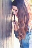 Mujer joven 15 Cabeza inclinada a la puerta y a las compresiones la manija ingenio imagen de archivo