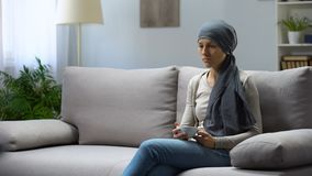 Mujer joven cansada con el cáncer que se sienta en casa y el té de consumición, remisión metrajes