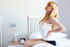 Mujer joven cansada con el dolor de espalda que se sienta en la cama en casa Fotografía de archivo