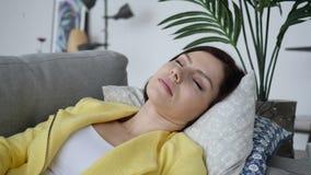 Mujer joven cansada durmiente que pone en el sofá en casa fotografía de archivo libre de regalías