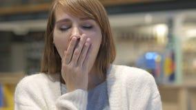 Mujer joven cansada que bosteza en el café, interior almacen de metraje de vídeo