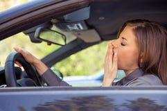 Mujer joven cansada que conduce el coche imagenes de archivo