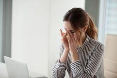Mujer joven cansada que da masajes al puente de la nariz en el lugar de trabajo imagen de archivo libre de regalías
