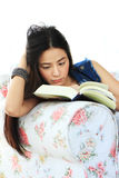 Mujer joven cansada que lee un libro en casa en el sofá Fotografía de archivo