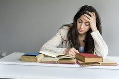 mujer joven cansada que se sienta en su escritorio con los libros en frente Foto de archivo
