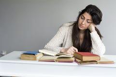 mujer joven cansada que se sienta en su escritorio con los libros en frente Foto de archivo libre de regalías