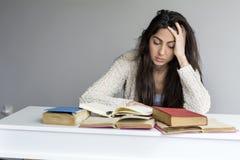 mujer joven cansada que se sienta en su escritorio con los libros en frente Fotos de archivo libres de regalías