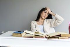 mujer joven cansada que se sienta en su escritorio con los libros en frente Fotografía de archivo
