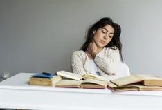mujer joven cansada que se sienta en su escritorio con los libros en frente Imagen de archivo libre de regalías