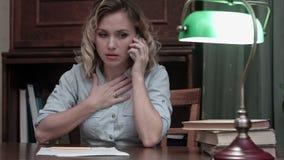 Mujer joven cansada que se sienta en su escritorio receiveing noticias muy malas en el teléfono almacen de metraje de vídeo