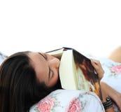 Mujer joven cansada que toma una siesta en casa que miente encendido tan Imagen de archivo