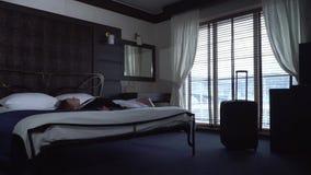 Mujer joven cansada y caídas en cama en la habitación La maleta llena se está colocando cerca almacen de metraje de vídeo