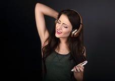 Mujer joven cantante hermosa que escucha la música en radio él Imagenes de archivo