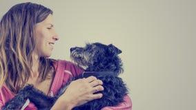 Mujer joven cariñosa con su perro casero fotos de archivo libres de regalías