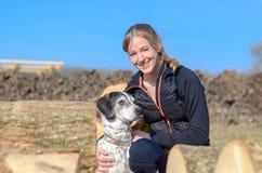 Mujer joven cariñosa feliz que abraza su perro Imagenes de archivo