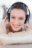 Mujer joven casual feliz que disfruta de música en el sofá Imagenes de archivo