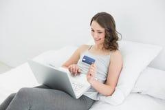 Mujer joven casual que hace compras en línea en cama Fotografía de archivo libre de regalías
