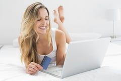 Mujer joven casual que hace compras en línea en cama Fotos de archivo