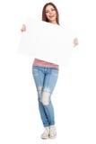 Mujer joven casual que lleva a cabo a un tablero blanco Imagenes de archivo