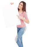 Mujer joven casual que lleva a cabo a un tablero blanco Foto de archivo