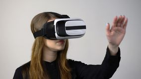Mujer joven casual que lleva las gafas de la realidad virtual que mueven la mano almacen de metraje de vídeo