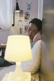 Mujer joven casual que se sienta en cama y que usa el ordenador portátil en casa Fotos de archivo