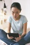 Mujer joven casual que se sienta en cama y que usa la tableta digital en casa Imagen de archivo