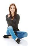 Mujer joven casual que se sienta en el piso blanco Fotografía de archivo