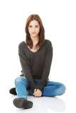 Mujer joven casual que se sienta en el piso blanco Imagen de archivo libre de regalías