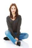 Mujer joven casual que se sienta en el piso blanco Foto de archivo