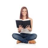 Mujer joven casual que se sienta en el piso que lee un libro Foto de archivo libre de regalías