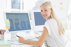 Mujer joven casual que usa el ordenador en oficina Fotografía de archivo libre de regalías
