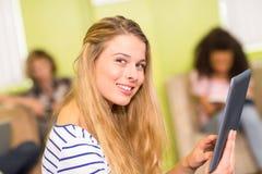 Mujer joven casual que usa la tableta digital en oficina Foto de archivo libre de regalías