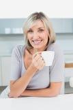 Mujer joven casual sonriente con la taza de café en cocina Fotografía de archivo