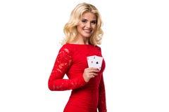 Mujer joven caucásica con el pelo rubio ligero largo en el equipo de la tarde que sostiene naipes Aislado póker fotografía de archivo