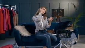 Mujer joven caucásica durante el vídeo que tira para el blog de la belleza almacen de metraje de vídeo