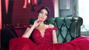 Mujer joven caucásica elegante atractiva de moda que presenta en vestido del encanto en la butaca de lujo almacen de video