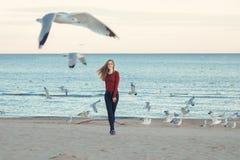 Mujer joven caucásica emocionada de risa sonriente en los vaqueros que corren el salto entre pájaros de las gaviotas Fotografía de archivo libre de regalías