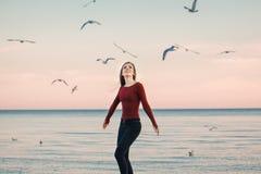 Mujer joven caucásica emocionada de risa sonriente en los vaqueros que corren el salto entre pájaros de las gaviotas Imagenes de archivo