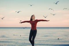 Mujer joven caucásica emocionada de risa sonriente en los vaqueros que corren el salto entre pájaros de las gaviotas Imagen de archivo