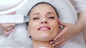 Mujer joven caucásica feliz que disfruta de procedimiento de peladura ultrasónico facial en el salón de belleza metrajes