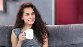 Mujer joven caucásica hermosa con el pelo rizado que se relaja en casa sosteniendo la taza blanca grande almacen de metraje de vídeo
