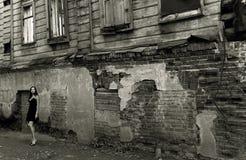 Mujer joven cerca de la casa arruinada con los ladrillos imagen de archivo