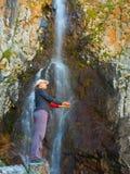 Mujer joven cerca de la cascada en las montañas, ala-Archa, Kyrgyzst Imagen de archivo libre de regalías