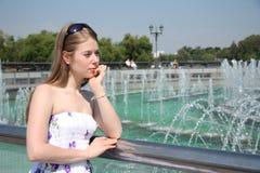 Mujer joven cerca de la fuente en un parque Imágenes de archivo libres de regalías
