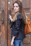 Mujer joven cerca de la puerta vieja Fotos de archivo