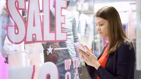 Mujer joven cerca de la tienda de ventana Venta rosada y amarilla Los QR-códigos de la lectura por el smartphone, comprobando val metrajes