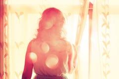 Mujer joven cerca de la ventana que espera alguien Fotos de archivo