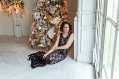 Mujer joven cerca de un árbol de navidad Imágenes de archivo libres de regalías